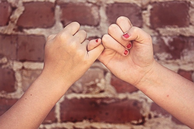 Friend hands pinky swear to keep a promise to pay them back